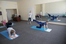 В зале ЛФК инструктор по лечебной физкультуре проводит групповое занятие лечебной гимнастикой. Подобраны комплексы для кардиологических больных, для больных с заболеваниями обмена, шейным и поясничным остеохондрозом.